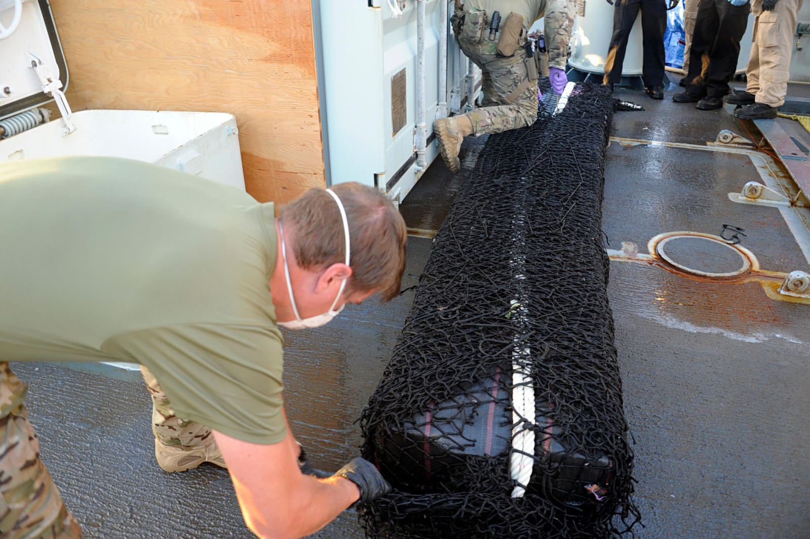 Two members of the United States Coast Guard cut the netting away from a large bale of cocaine on the deck of HMCS Whitehorse, part of the 1,500 kg of cocaine seized on April 5, 2018 during Operation CARIBBE. Photo: MARPAC Public AffairsXC052-2018-0001-111~Deux membres la garde c?ti?re des ?tats Unis se trouvant sur le pont du NCSM Whitehorse coupent le filet entourant un grand ballot de coca?ne faisant partie des 1 500 kg de coca?ne qui ont ?t? saisis le 5 avril 2018, dans le cadre de l?op?ration CARIBBE. Photo : Affaires publiques des FMAR(P)XC052-2018-0001-111